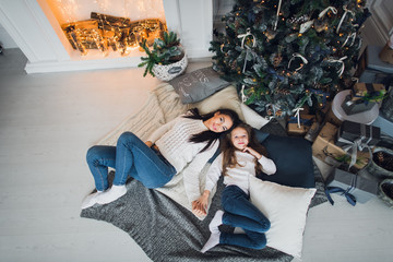 Forever best friends. Top view of happy mom and her daughter wearing jeans and white sweathers lying together on the blanket relaxing at home under christmas tree with gifts and fireplace nearby on a