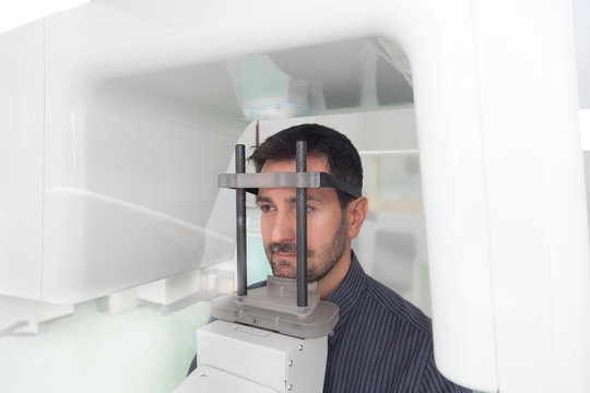 A handsome man having panoramic digital x-ray of his teeth.