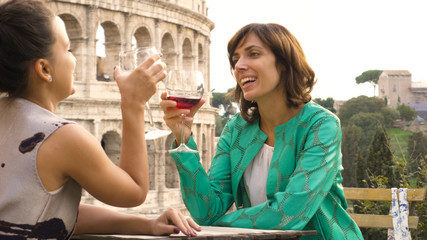 Two happy young woman tourists sitting at the table of a bar restaurant in front of the Colosseum in Rome drink and toast with a glass of italian red wine. Stylish colorful dress on a summer day at