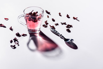 glass cup of hibiscus tea with spoon and scattered tea on table
