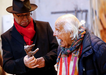 Berlinale International Film Festival director Dieter Kosslick holds a Berlin Bear award cast as Hermann Noack, owner of the Noack foundry reacts during a media event for the upcoming film festival at the Noack foundry in Berlin