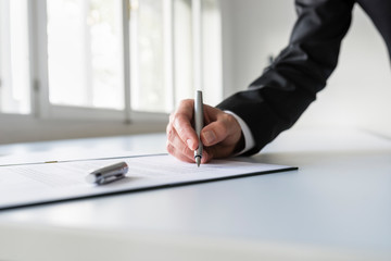 Man in business suit signing contract