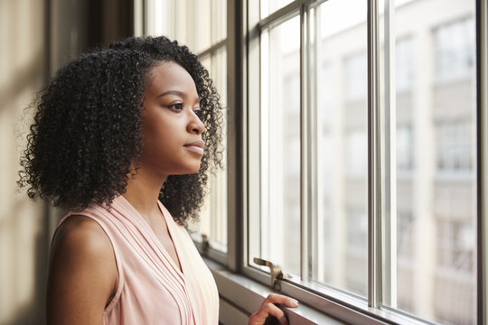 Young black businesswoman looking out of window