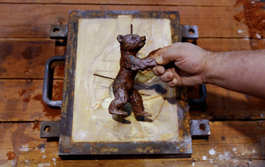 A worker poses with a casting mould of a Berlin Bear award for the upcoming Berlinale International Film Festival at the Noack foundry in Berlin