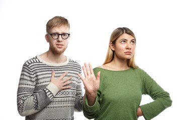 Studio shot of displeased blonde girl showing stop sign with her palm, meaning It's over while her unhappy miserable boyfriend with unhappy look holding hand on his chest as sign of broken heard
