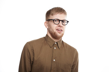 Horizontal shot of young bearded male of European appearance wearing eyeglasses and shirt having disgusted displeased expression, staring at camera with disgust. Human emotions and reaction
