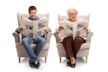 Young man and an elderly woman sitting in armchairs and reading newspapers