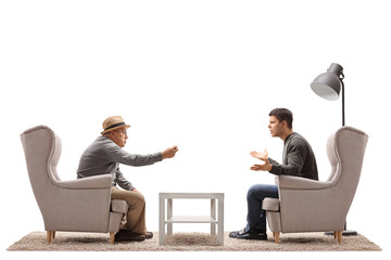 Mature man and a young guy seated in armchairs arguing