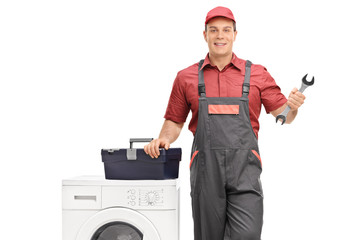 Repairman holding a wrench next to a washing machine