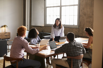 Smiling woman standing to address colleagues at a work meeting