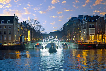 Canvas Prints Amsterdam Amsterdam lights in the city center at the river Amstel in the Netherlands at sunset