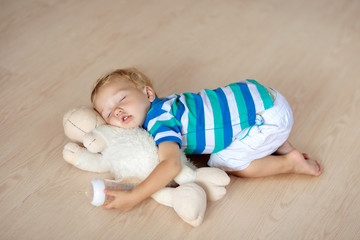 Baby sleeping on floor with toy and milk bottle.