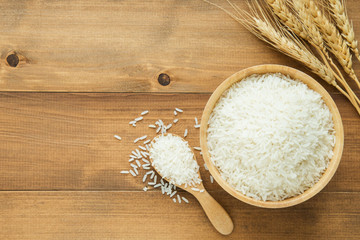 white rice (Thai Jasmine rice) in wooden bowl on wood background with copy space
