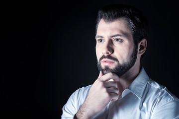 Full of thoughts. Portrait of a nice handsome thoughtful man holing his chin while thinking
