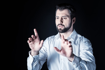 Professional technology. Nice handsome serious man standing against black background and looking at the virtual screen while using virtual technology