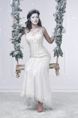 Beautiful snow maiden on swing
