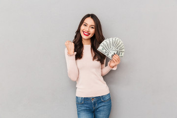 Image of lucky brunette female holding fan of 100 dollar bills being excited to win cash prize expressing victory and wealth over gray wall