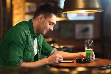 man with smartphone and green beer texting at bar