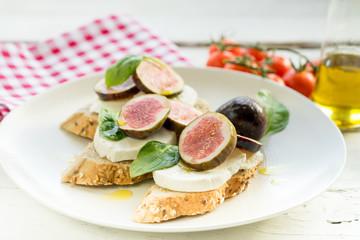 fresh ripe sliced fig on toast bread mozzarella cheese Italian crostini dish light lunch starter