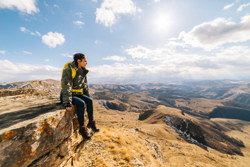 active young girl sits on the edge of the cliff, enjoys the mountain nature and the sun