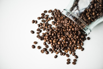 top view of scattered coffee beans from glass bottle isolated on white