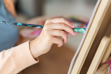 hand of artist with brush painting at art studio