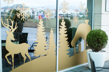 glass wall decorated with a large sticker with Santa Claus and deer