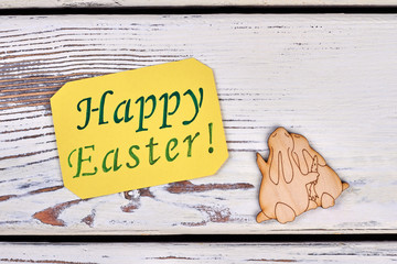 Happy Easter card and plywood rabbits. Yellow paper message with text Happy Easter and couple of plywood bunnies on white wooden background. Easter holidays congratulations.