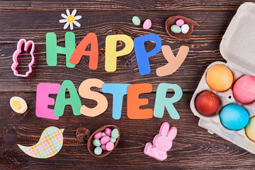 Happy Easter colorful letters. Colorful paper Easter greeting text, sweets and eggs on wooden table. Happy Easter composition on brown wooden background.