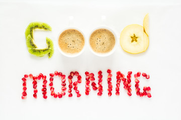 Good morning concept. 'Good morning' words laid out with pieces of fruit and pomegranate seeds. Lovely message. Flat lay. Top view. Space for copy
