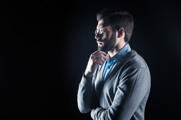 Process of thinking. Nice handsome serious man holding his chin and focusing on his thoughts while standing against black background