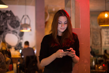 Young woman with long dark hair stands in middle of bar or cafe, her face lit up by light from smartphone screen, texts or chats on social media instead of talking to real people. internet addiction
