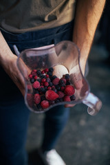 Soft focus of man holds blender or food processor with frozen forest berries, organic bananas and ice cream. Preparation recipe for smoothie or healthy blended drink for fitness diet