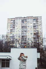 Young man photographer, walks and explores urban soviet city architecture. Smartphone influencer or blogger makes photos for social media