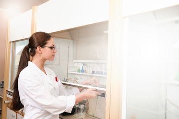 Young woman sciencist in laboratory near equipment
