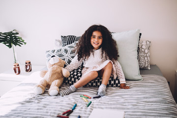Little african girl sitting on bed with teddy bear smiling