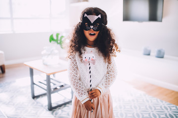 Happy Little girl in costume with cat mask at home