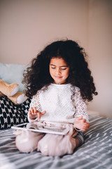Girl playing game on digital tablet at home
