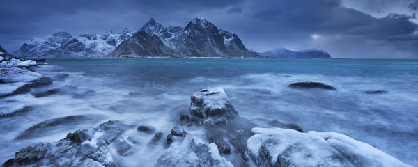 Fototapete - Dark clouds over a fjord in Norway in winter