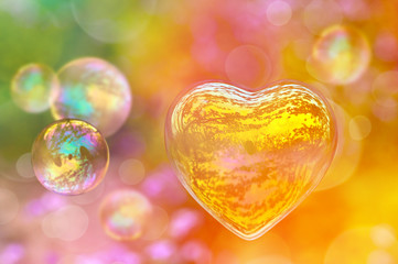 Soap bubble in the shape of a heart, colorful background