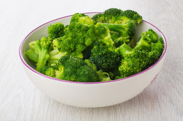 Cooked broccoli in glass bowl on table