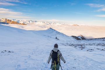 Backpacker hiking on snow on the Alps. Rear view, winter lifestyle, cold feeling, majestic mountain landscape.
