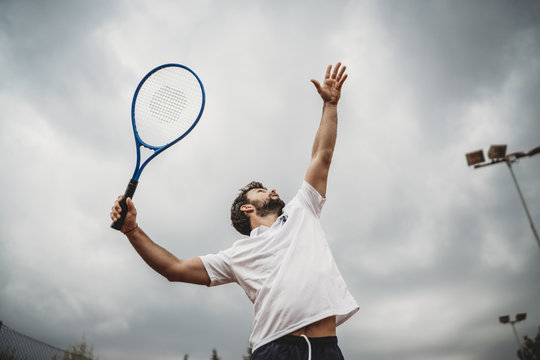 Young man engaged in the tennis service during a match