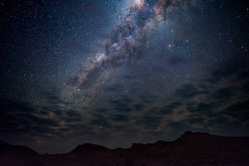 Milky Way arch, stars in the sky, the Namib desert in Namibia, Africa. Some scenic clouds.