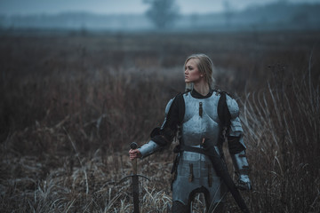 Girl in image of Jeanne d'Arc in armor and with sword in her hands stands on meadow. Closeup.