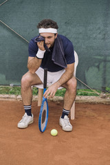 A young man having a break after a tennis match on a clay court