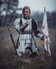 Girl in image of Jeanne d'Arc in armor kneels with flag in her hands and sword on meadow.