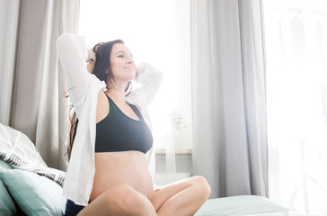 Happy pregnant woman at home sitting on sofa