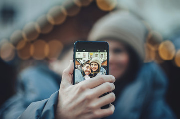 Young beautiful cheerful couple taking a selfie in the city stre