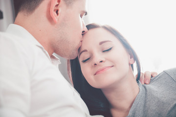 Beautiful couple kissing and hugging at home near window with sunlight